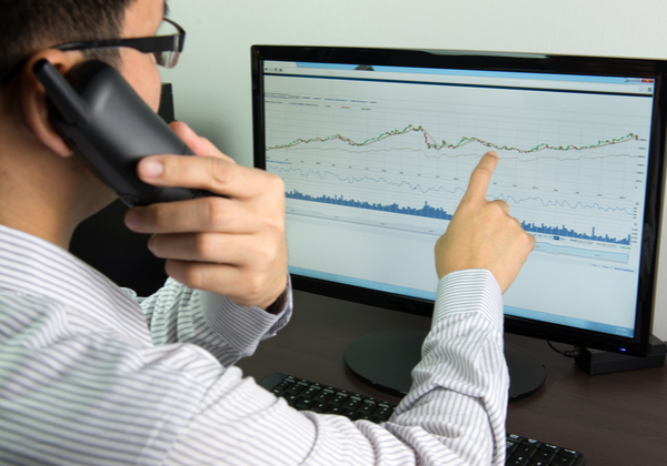 Businessman pointing at the chart on computer screen while talking on the phone