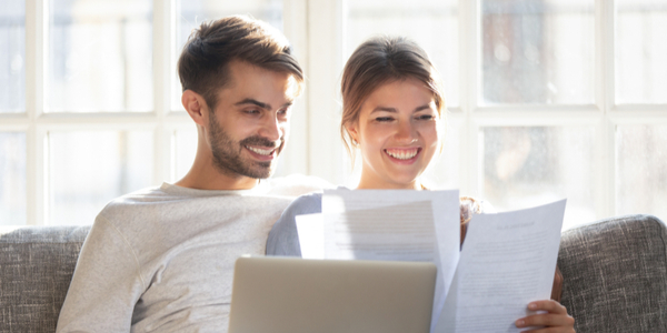Happy young couple relax on sofa read paperwork