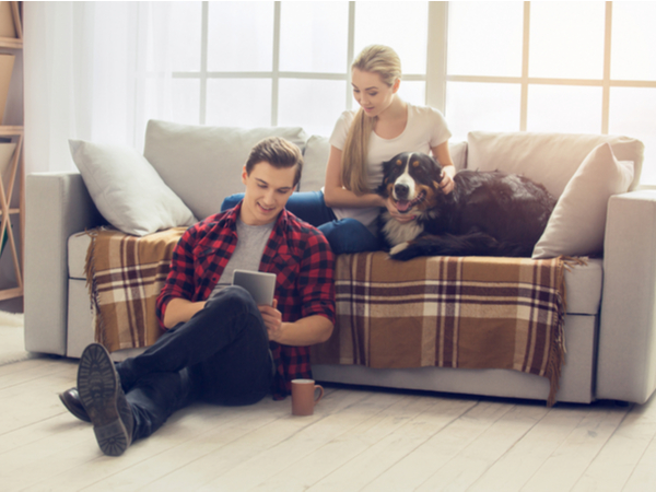 Man holding the tablet and a girl sitting on the couch with a dog