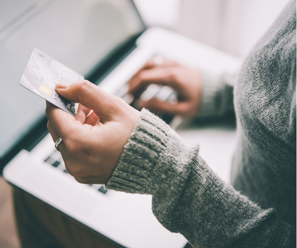 Hands holding plastic credit card and using laptop