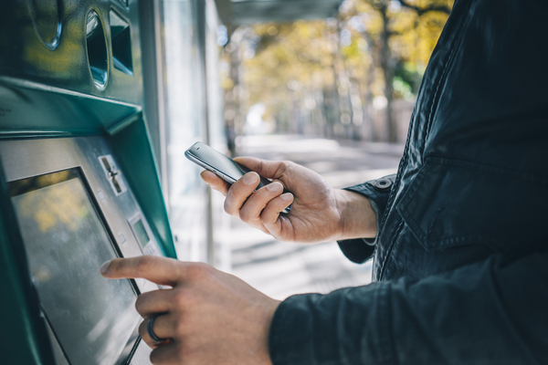 Male hands using smart phone while typing on ATM