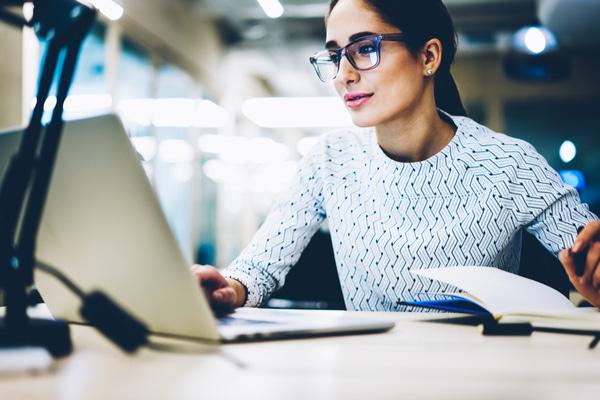 Businesswoman reading publication via laptop
