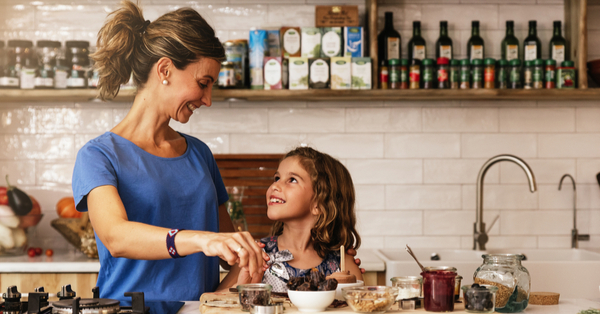Little girl cooking with her mother in the kitchen