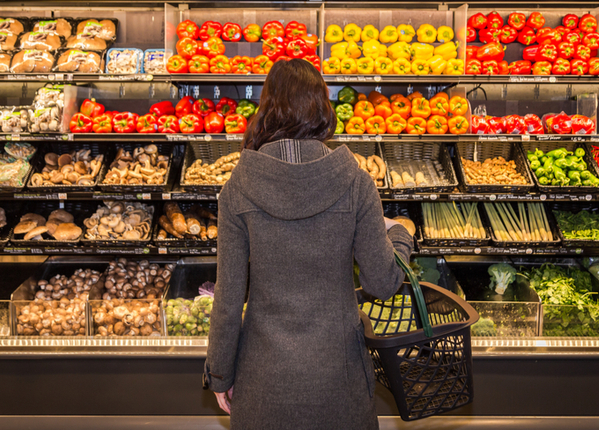Woman standing in front of a row of produce in a grocery store