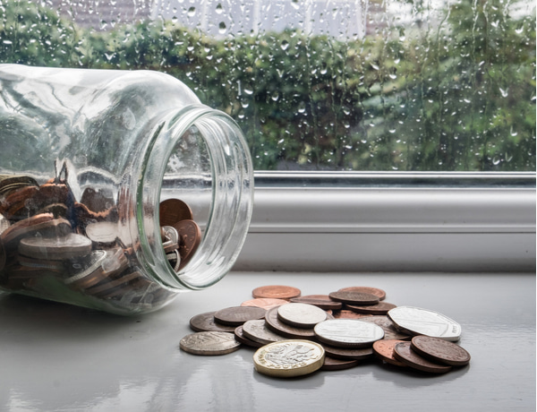 Jar of english money with rainy day background