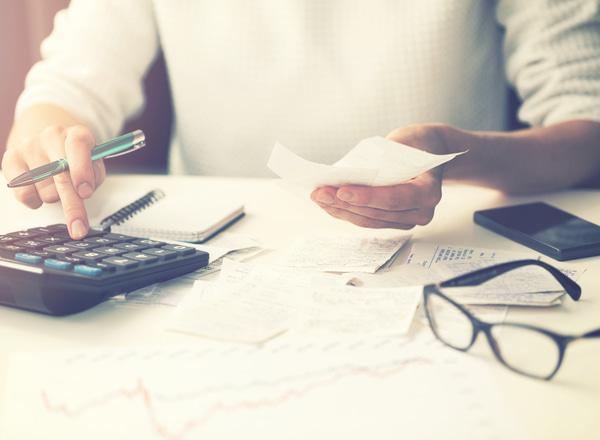 Woman calculating bills at home
