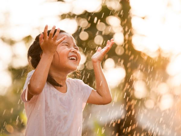 Happy kid playing in the rain