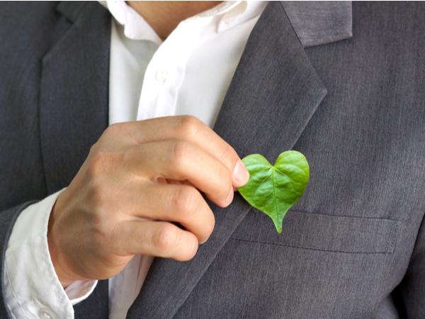 Man wearing a coat holding a heart-shaped leaf