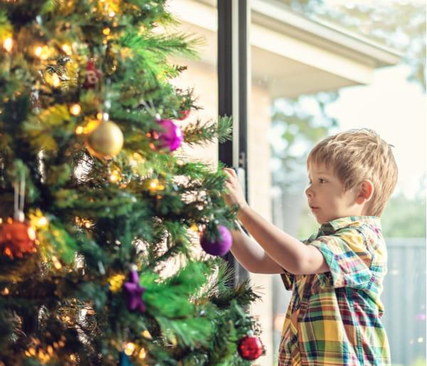 Cute little boy decorating a Christmas tree