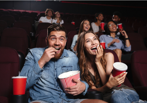 SU - Happy couple eating popcorn while swatching movie