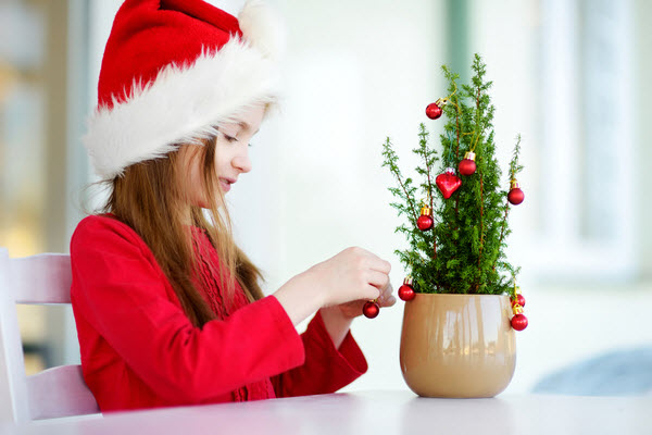 Adorable little girl wearing Santa hat decorating small Christmas tree