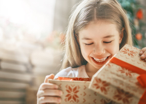 Happy girl child opening gift at Christmas