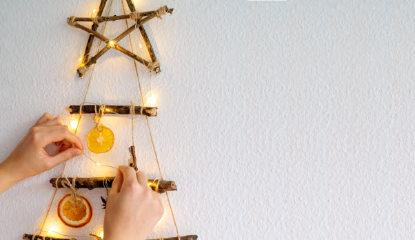 hands of a woman decorating handmade craft Christmas tree made with natural materials and lights hanging on wall