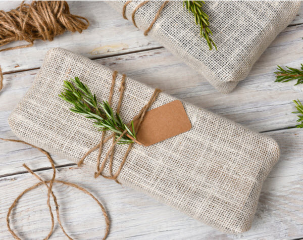 Fabric wrapped Christmas presents placed on a rustic wood table.