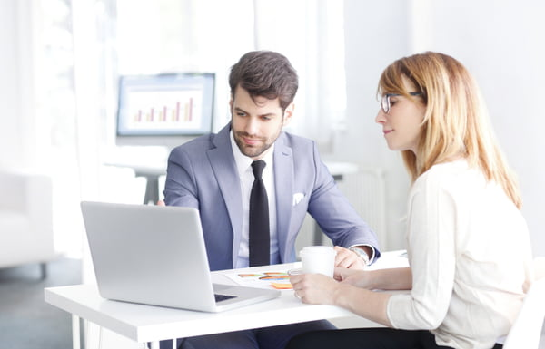 Bank officer consulting with businesswoman while sitting at office