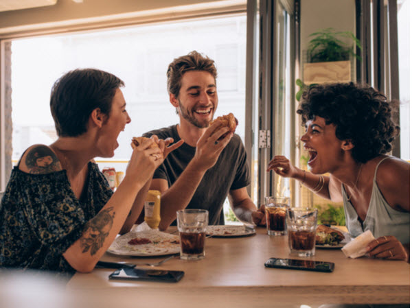Cheerful young people eating burger and enjoying at a restaurant.