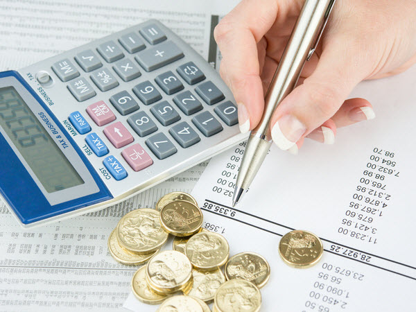 Woman computing her funds with coins and calculator on top of the paper