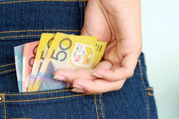 Woman's hand taking out money from the pocket of her jeans
