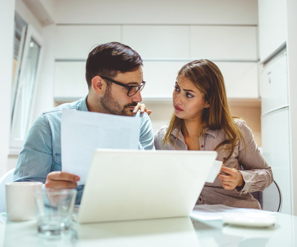 Young couple looking stressed while going over their finances at home