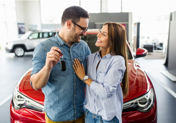 Beautiful young smiling couple holding a key of their new car