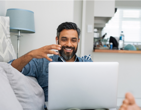 Happy mature man relaxing on couch while video calling