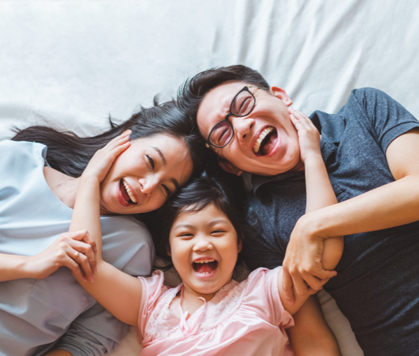 Happy Asian family laying on bed in bedroom