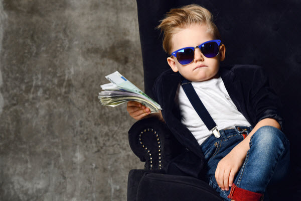 A little boy wearing sunglasses while sitting and holding a money