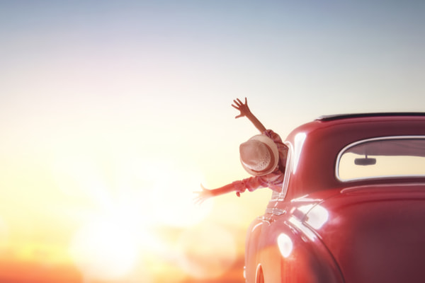 Happy girl rides into the sunset in vintage car