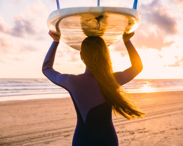 Woman with surfboard on a beach at sunset