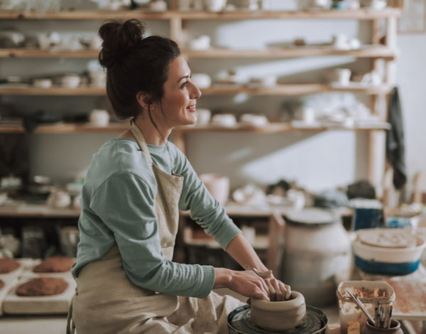 Beautiful craftswoman making clay bowl in pottery workshop