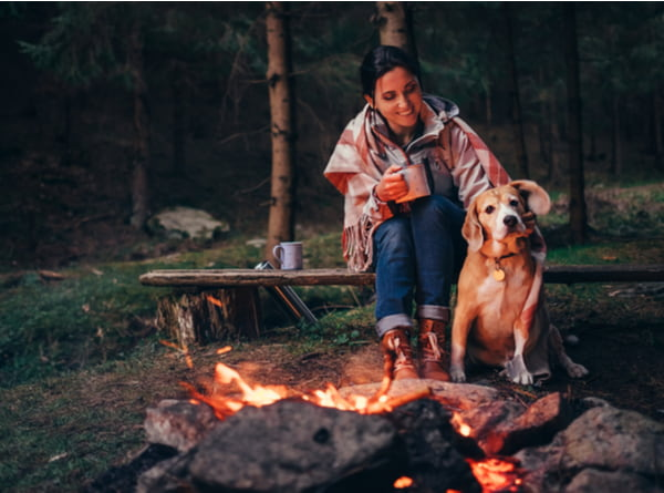 Woman and dog warm near campfire in forest