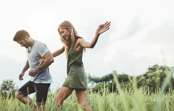 Couple walking through meadow hand in hand