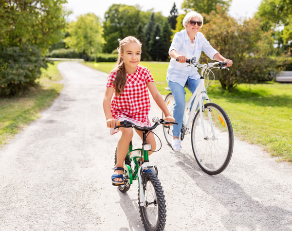 Grandmother and granddaughter riding bicycles