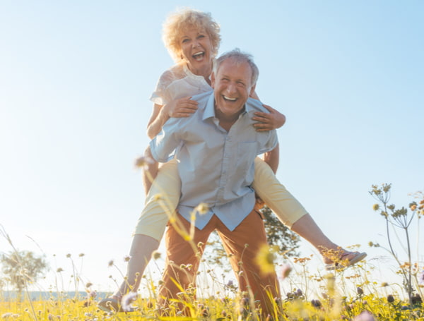 Senior man laughing while carrying his partner on his back