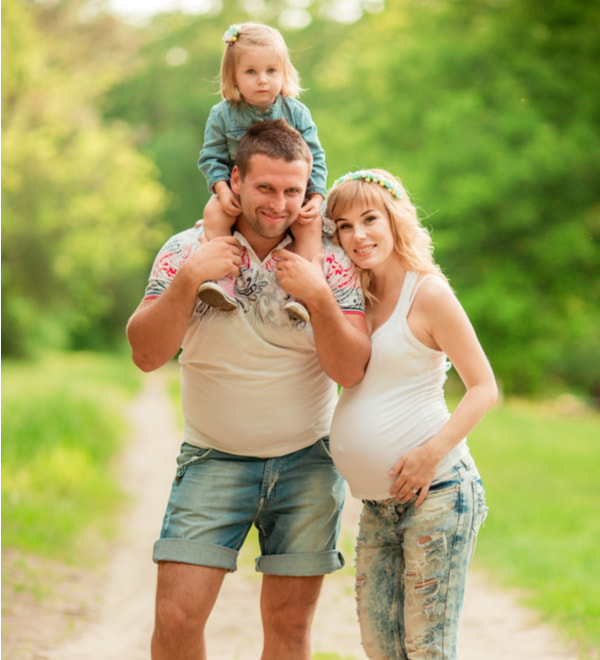 Beautiful pregnant woman with her husband and young daughter in green garden